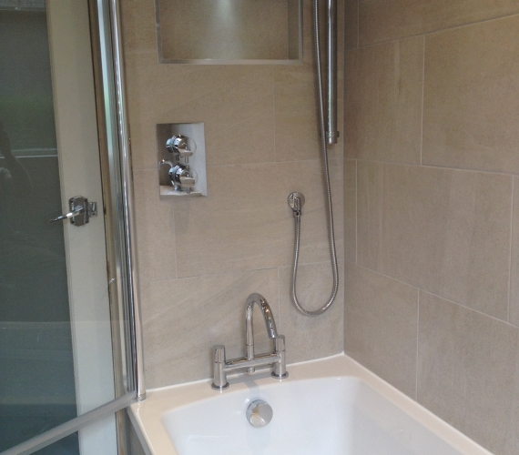 Concealed shower valve - riser rail - bath mixer taps - niche boxing with LED deck light.