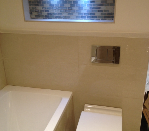 BTW W/C with Geberit concealed cistern and flush plate - mosaic tiled niche boxing.