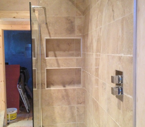 Fixed shower head and separate valve - Natural stone tile.