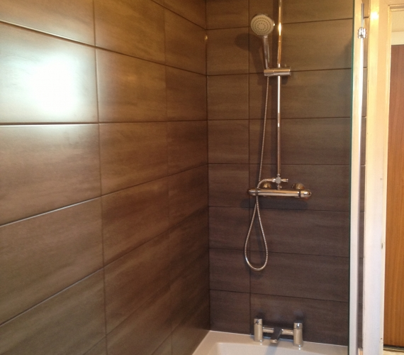 Thermostatic bar shower over bath. Charcoal tile with black grout.